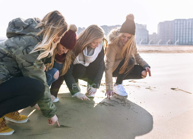 Four young women drawing in the sand on the beach — Stock Photo