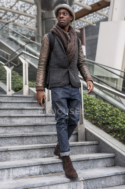 Stylish man wearing autumn fashion walking down stairs — Stock Photo