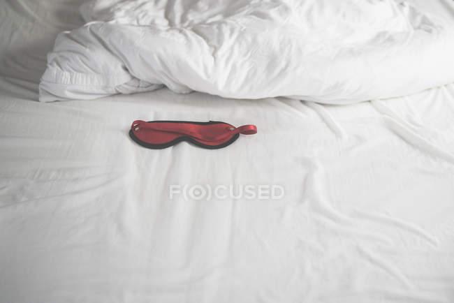 Красный глаз маска в смятой кровати — стоковое фото