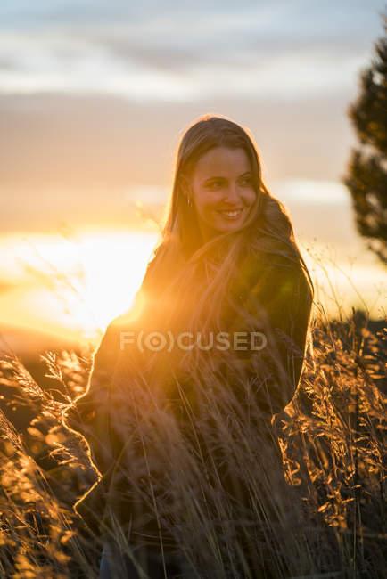 Femme debout dans la nature au coucher du soleil — Photo de stock