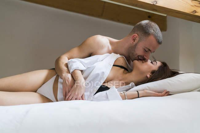 Paar kuscheln im Bett, Dachboden innen liegend — Stockfoto