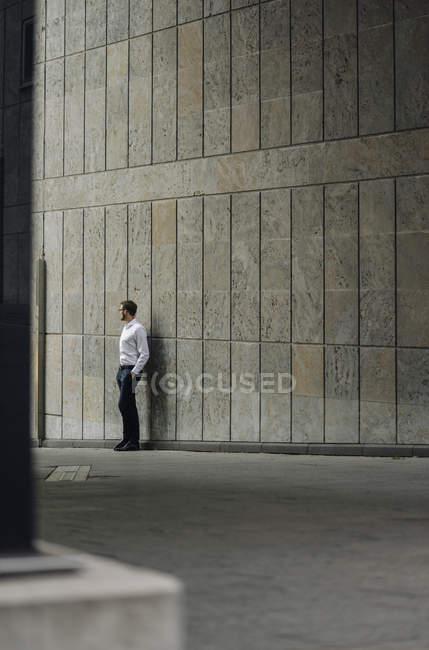 Портрет бізнесмен, стоячи біля будівлі стіни — стокове фото