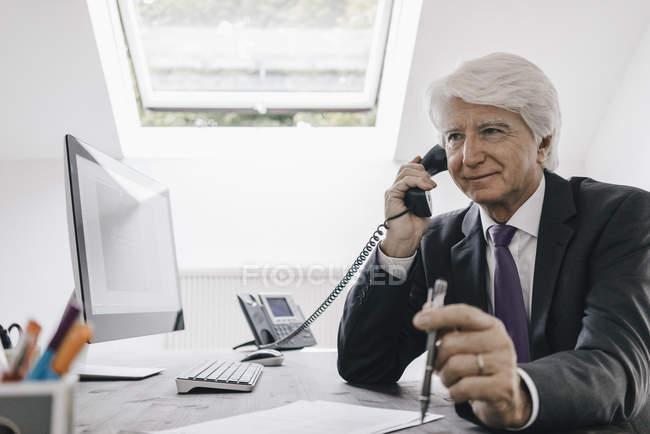 Retrato de empresário usando telefone à mesa — Fotografia de Stock