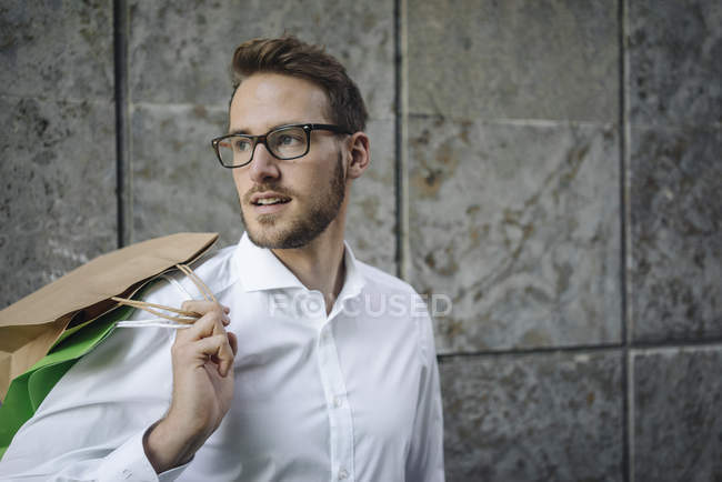 Portrait of businessman holding shopping bags — Stock Photo