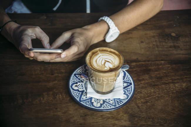 Mãos femininas usando telefone celular em um café com copo de café — Fotografia de Stock