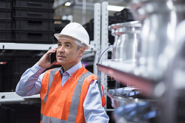 Man on cell phone standing in factory — Stock Photo