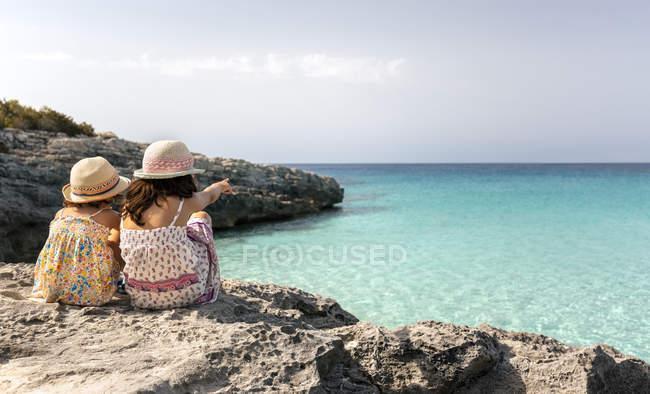 Praia Talaier, Ilhas Baleares, Espanha, duas meninas olhando para o horizonte na costa — Fotografia de Stock