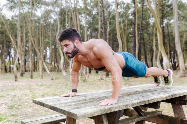 Сорочки людина робить віджимання на дерев'яний стіл на відкритому повітрі — Stock Photo