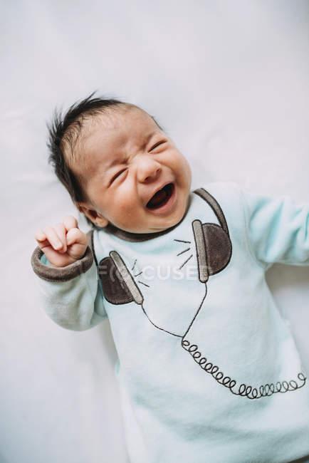 Menina de bebê recém-nascido chorando na cama — Fotografia de Stock