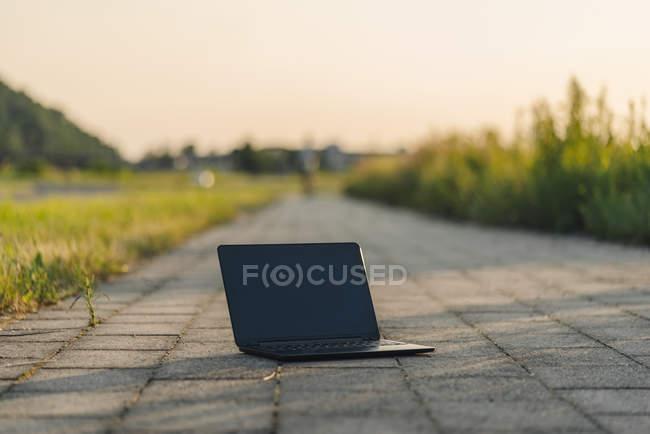 Дневной просмотр черного ноутбука на дороге в парк — стоковое фото
