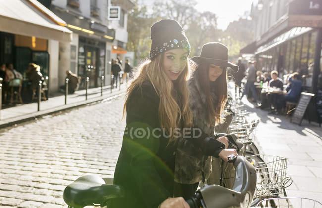 Paris, France, deux touristes féminines en vélo public — Photo de stock