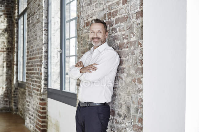 Businessman leaning against brick wall — Stock Photo