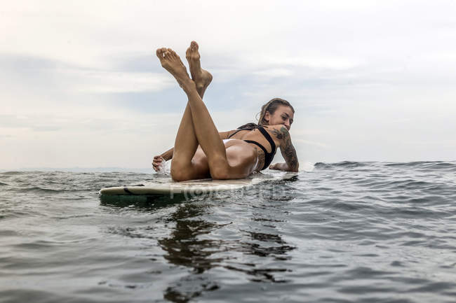 Indonesia, Java, woman lying on surfboard on the sea — Stock Photo