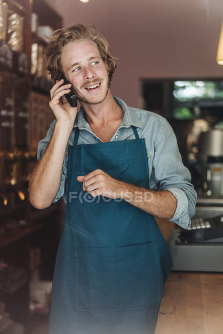 Smiling coffee roaster in shop on the phone — Stock Photo
