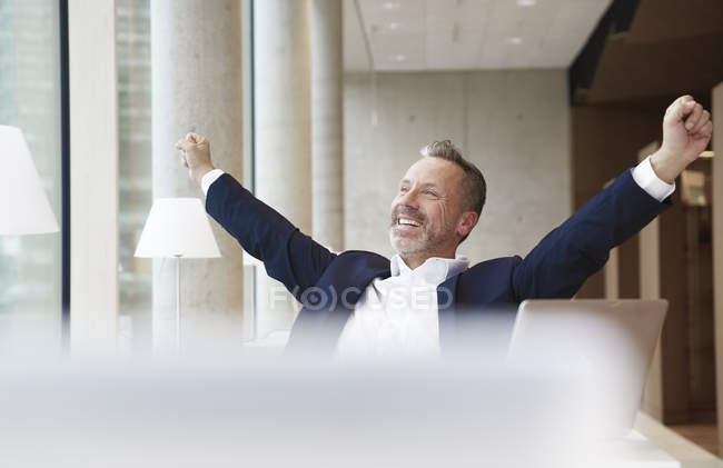 Businessman stretching in office — Stock Photo