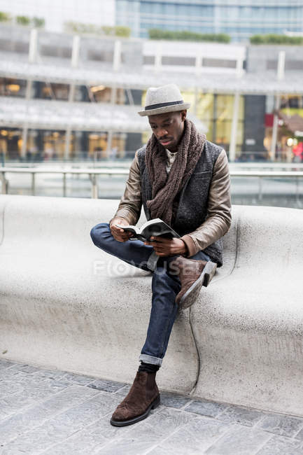 Young man sitting on bench and reading a book — Stock Photo