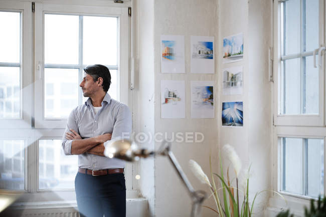 Thoughtful man looking out of window in office — Stock Photo