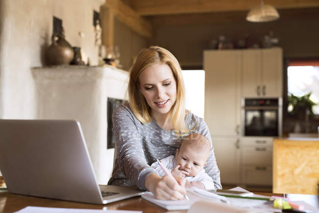 Mother with baby using laptop and taking notes at home — Stock Photo