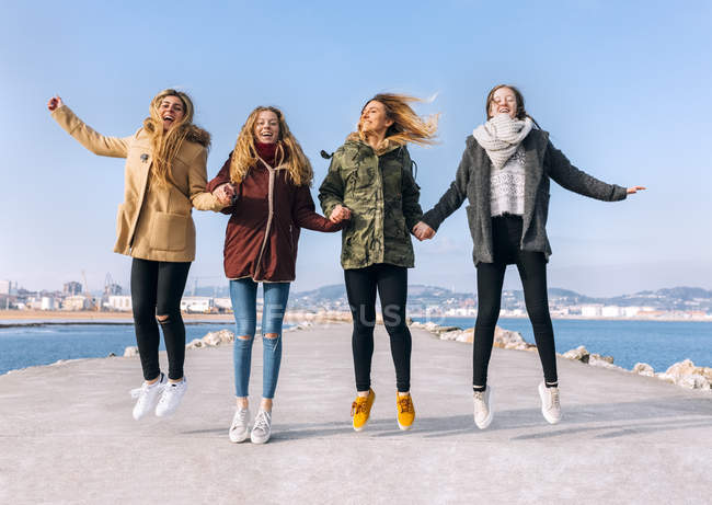 Four young women jumping on pier — Stock Photo