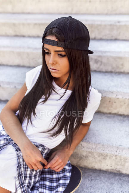 Gijn, Asturias, Spain, skateboarder girl sitting on street stairs — Stock Photo
