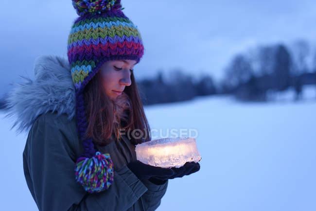 Souriant adolescent fille tenant gâteau en glace avec bougie à l'intérieur — Photo de stock