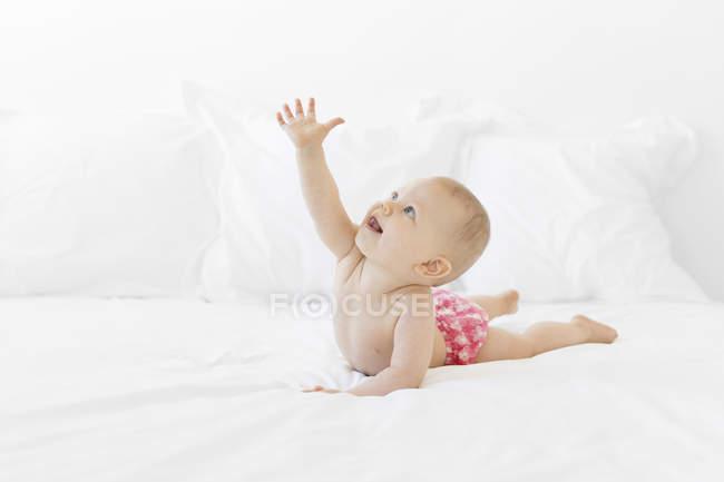 Baby liegt auf weißem Bettlaken und streckt den Arm — Stockfoto