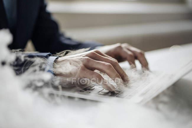 Обрізаний подання чоловічої руки набравши на ноутбуці куріння — стокове фото