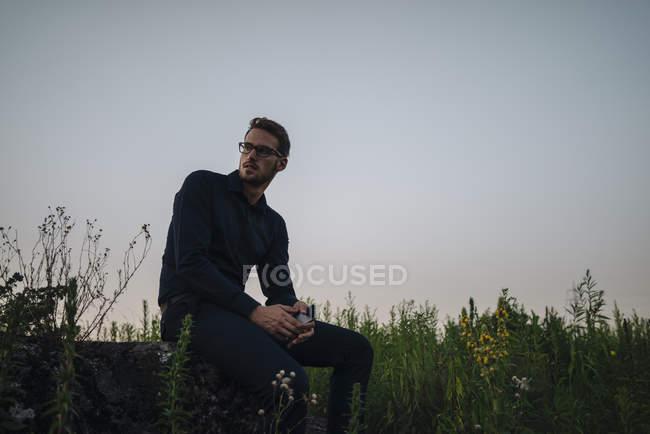 Retrato do empresário sentado com telefone móvel em bloco de cimento — Fotografia de Stock