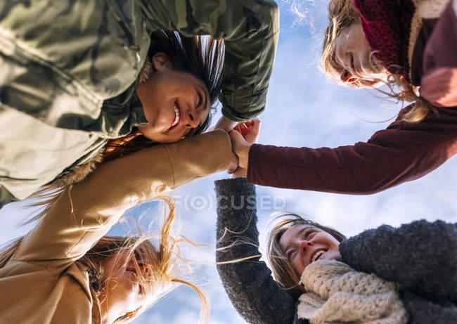 Quattro amici che unisce le mani con il cielo nuvoloso su priorità bassa — Foto stock