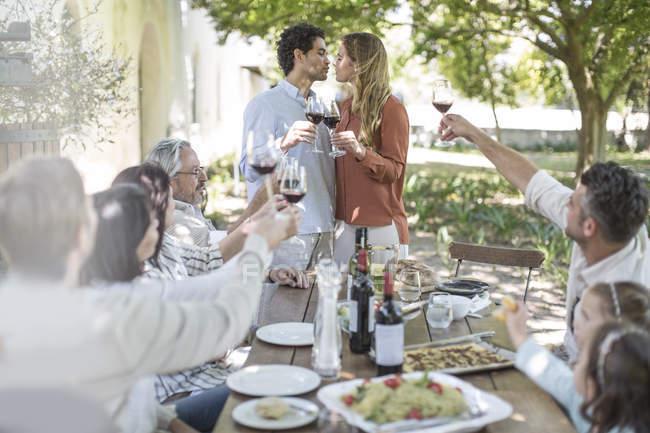 Couple baiser ensemble comme des amis et la famille déclenche un toast avec verres à vin en dehors des repas jardin — Photo de stock