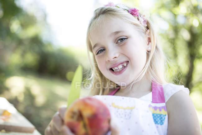 Ritratto di ragazza sorridente che tiene la pesca all'aperto — Foto stock