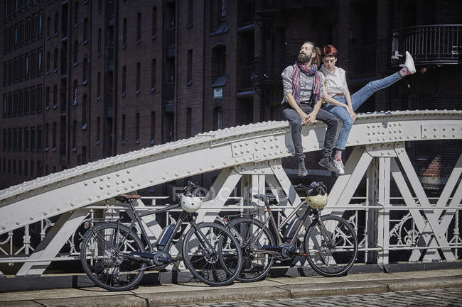 Portrait of cyclists couple resting on bridge — Stock Photo