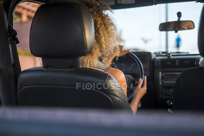 Rear view of woman driving car — Stock Photo