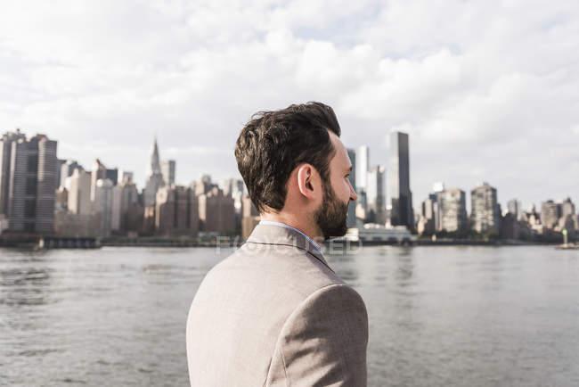 Homem de pé em East River em frente ao horizonte de Manhattan, Nova York, EUA — Fotografia de Stock