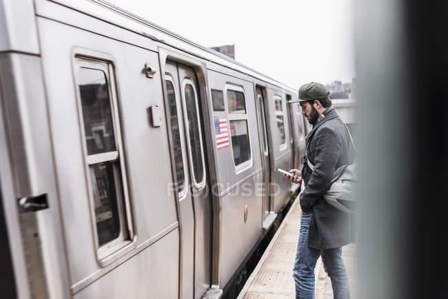 Человек ждет метро на вокзале — стоковое фото