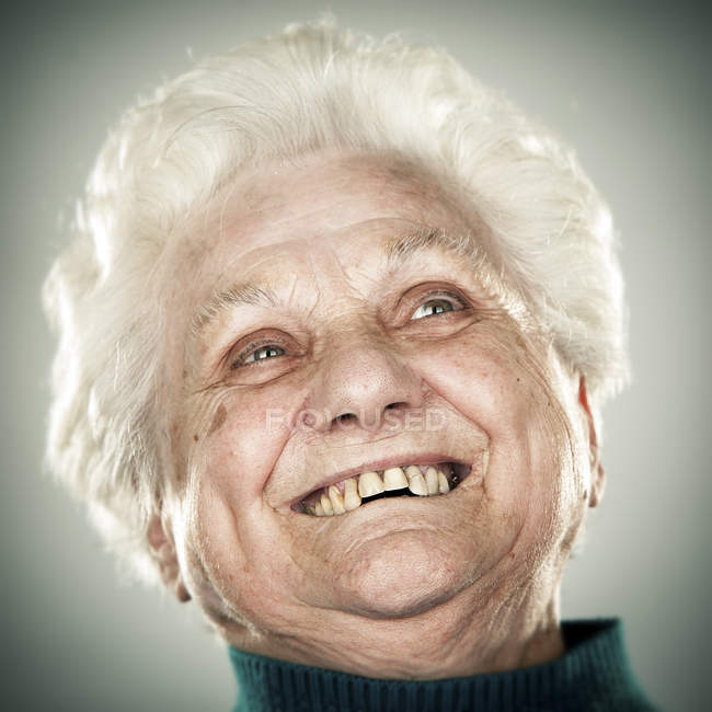 Portrait of smiling senior woman looking up — Stock Photo