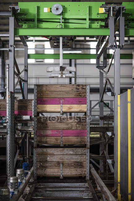 Group of crates stacked on machine in factory — Stock Photo