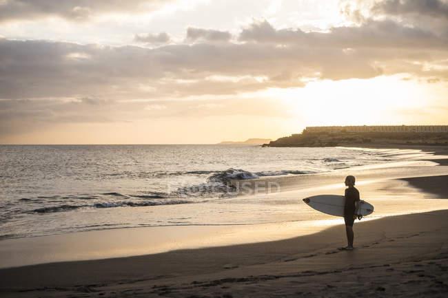 Vue lointaine de adolescent garçon portant planche de surf sur la plage à beau coucher de soleil — Photo de stock