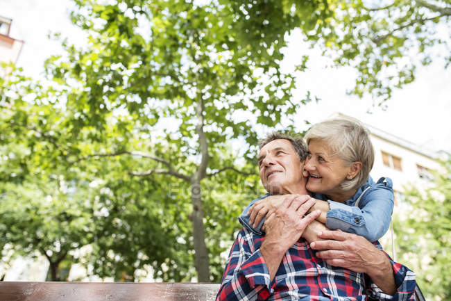 Happy cute senior couple hugging on bench at park — Stock Photo