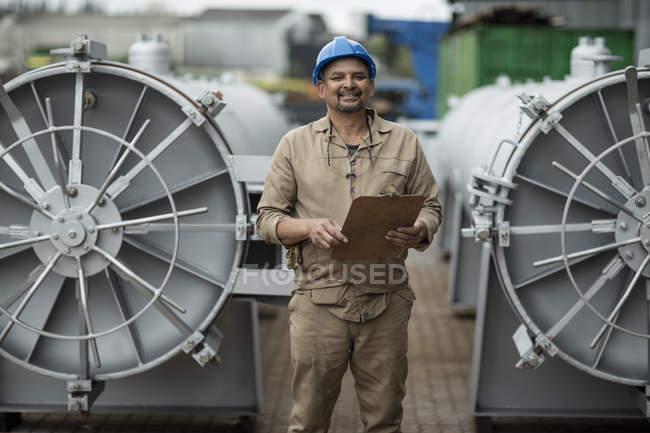 Worker in factory checking horizontal retorts — Stock Photo