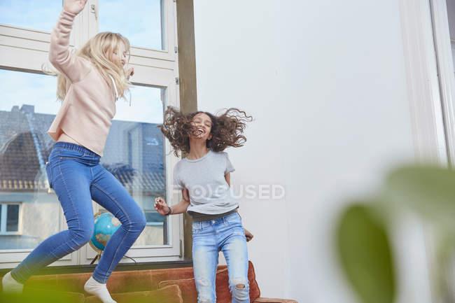 Due ragazze entusiaste saltando e ballando a casa — Foto stock