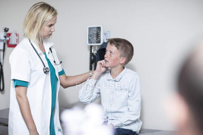 Pedeatrician feminino menino examinando com um otoscópio — Fotografia de Stock