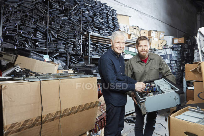 People workinhg in storage of computer recycling plant — Stock Photo