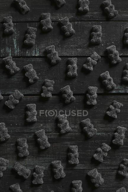 Osos gomosos negros sobre fondo de madera - foto de stock