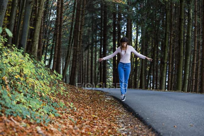 Молода жінка, балансуючи на узбіччі дороги в лісі — стокове фото