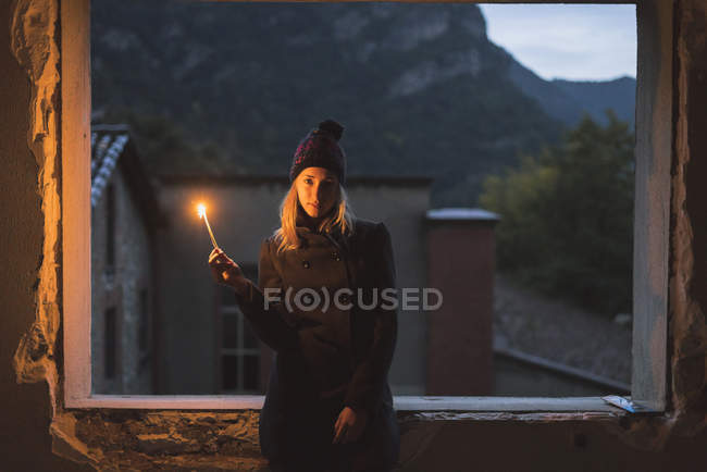 Young woman shining light at dusk — Stock Photo