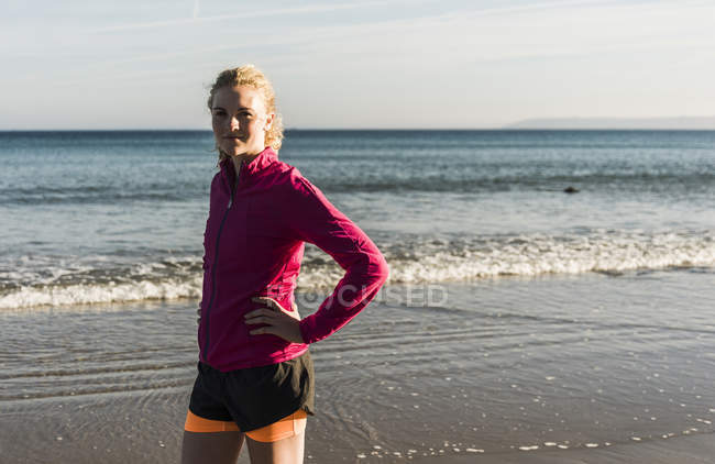 Sportive teenage girl standing on the beach and looking at camera — Stock Photo