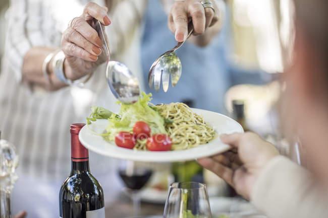 Vista recortada de la mujer repartiendo el almuerzo en el plato - foto de stock