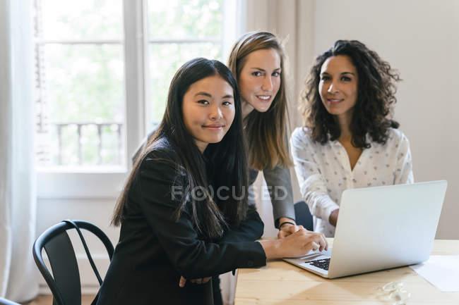 Three businesswomen working together on laptop — Stock Photo