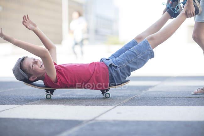 Bambini felici a scherzare con skateboard sulla strada — Foto stock